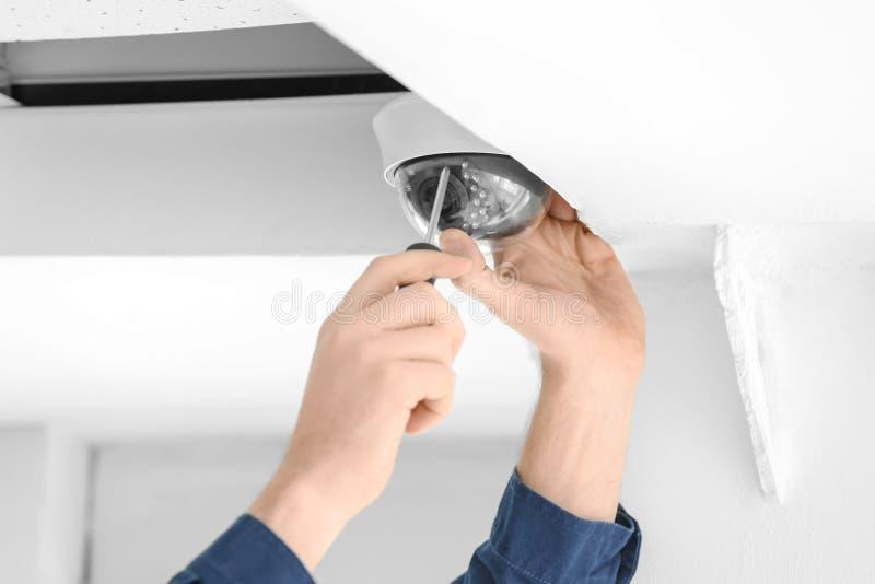 Tecnico che installa la macchina fotografica del CCTV sul soffitto all'interno, primo piano immagine stock libera da diritti