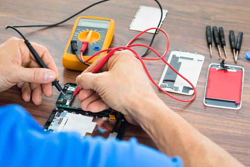 Tecnico che ripara cellulare con il multimetro fotografia stock