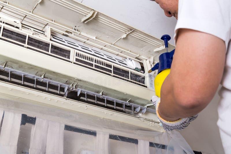 Tecnico che spruzza acqua chimica sulla griglia del condizionatore d'aria a fotografia stock