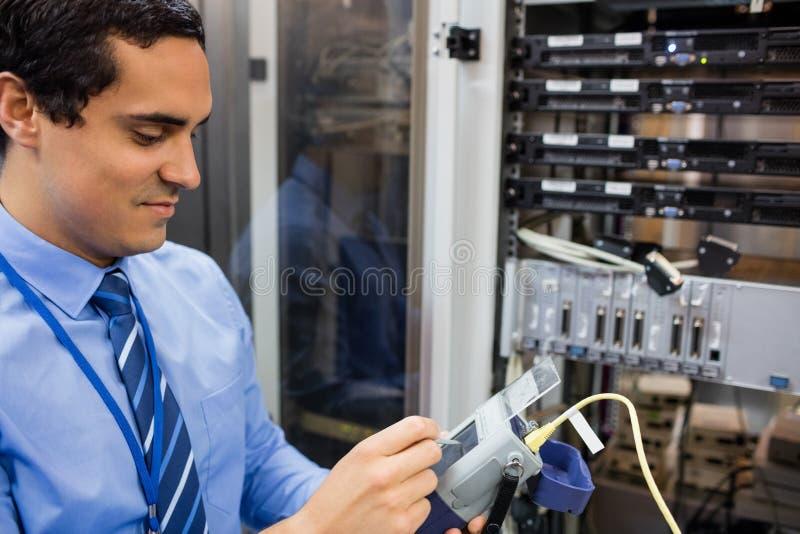 Tecnico che usando l'analizzatore digitale del cavo immagine stock