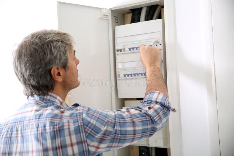 Tecnico che verifica la scatola elettrica a casa immagini stock