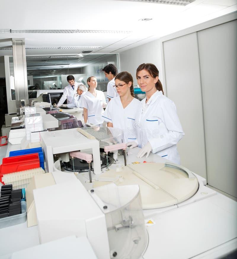 Tecnico And Colleague Working in laboratorio immagini stock