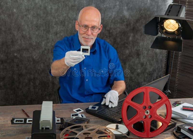 Tecnico con i guanti bianchi che digitalizzano il vecchio scorrevole di film di 35mm fotografie stock