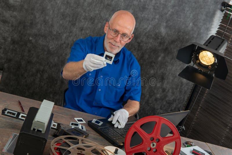 Tecnico con i guanti bianchi che digitalizzano il vecchio scorrevole di film di 35mm immagini stock libere da diritti