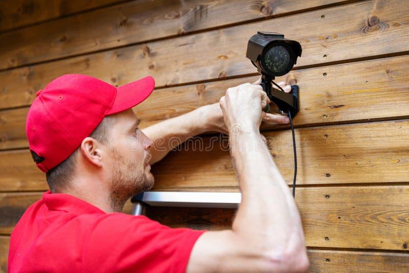 Tecnico del sistema di sicurezza che installa videosorveglianza sulla parete di legno della casa fotografia stock