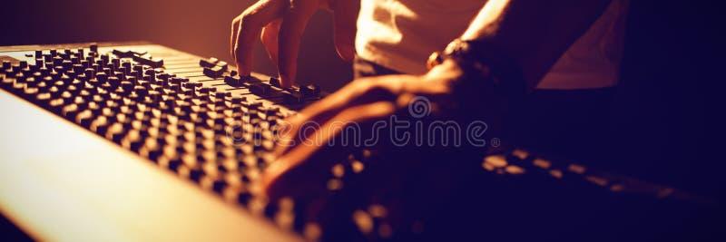 Tecnico del suono di funzionamento del DJ in night-club illuminato fotografie stock libere da diritti