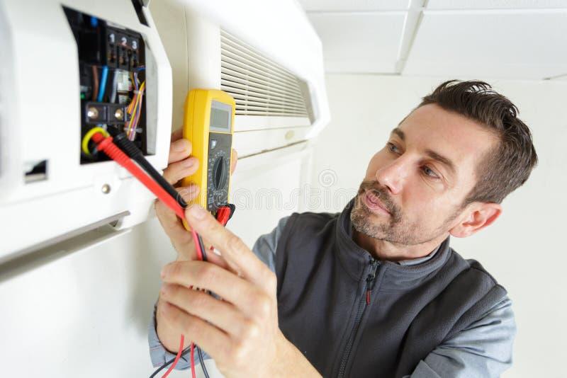 Tecnico dell'elettricista che lavora al pannello elettrico residenziale fotografia stock