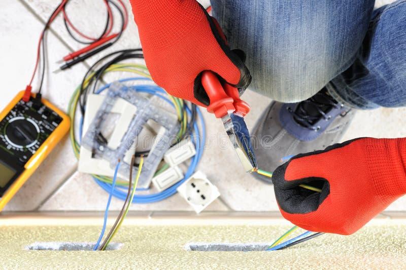 Tecnico dell'elettricista sul lavoro con l'attrezzatura di sicurezza su un sistema elettrico residenziale fotografie stock