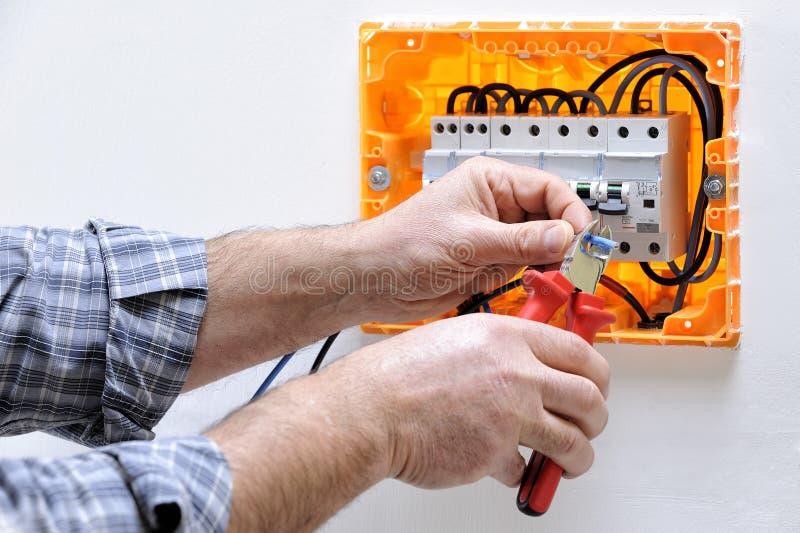 Tecnico dell'elettricista sul lavoro su un pannello elettrico residenziale immagini stock