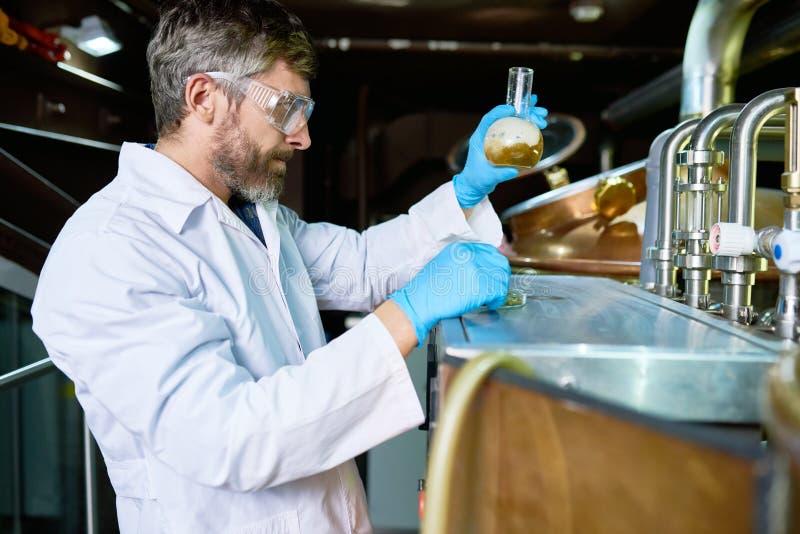 Tecnico facente moderno che crea la birra del mestiere nella pianta fotografia stock
