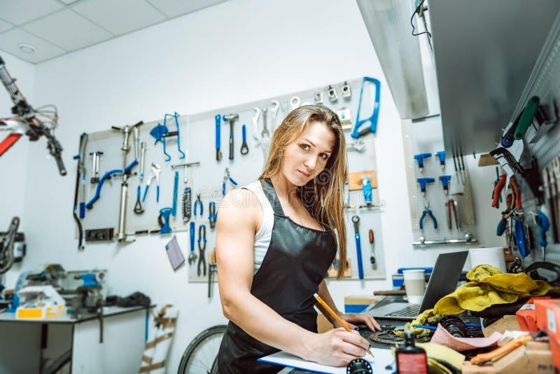 Tecnico femminile bello che emette un progetto nell'officina fotografie stock