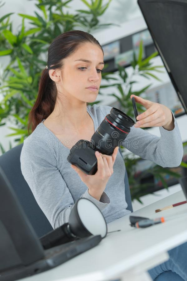 Tecnico femminile che fa la macchina fotografica di manutenzione immagine stock libera da diritti