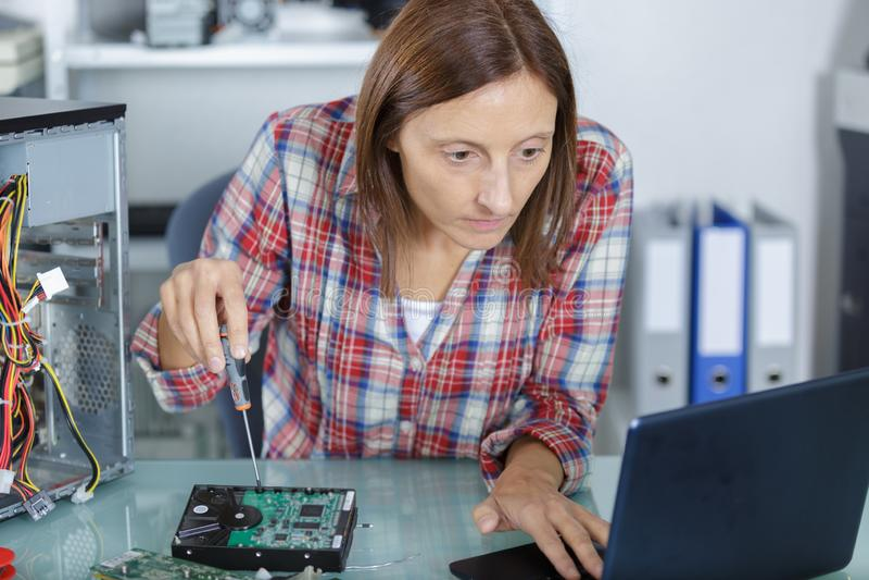 Tecnico femminile del pc che esamina esercitazione per il computer di riparazione immagine stock