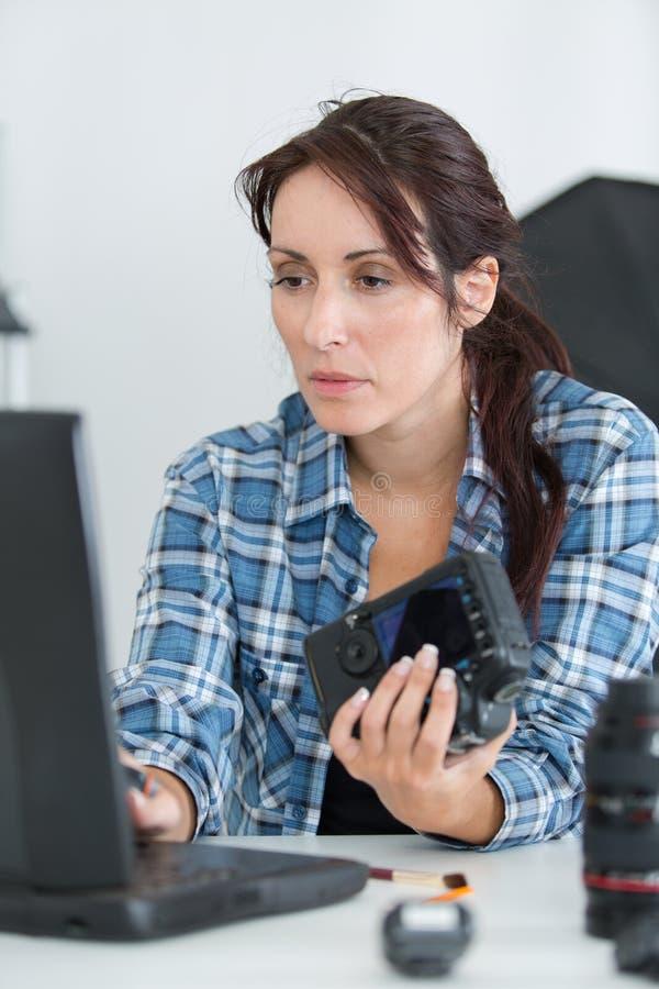 Tecnico femminile della macchina fotografica che scrive sul computer portatile fotografia stock libera da diritti