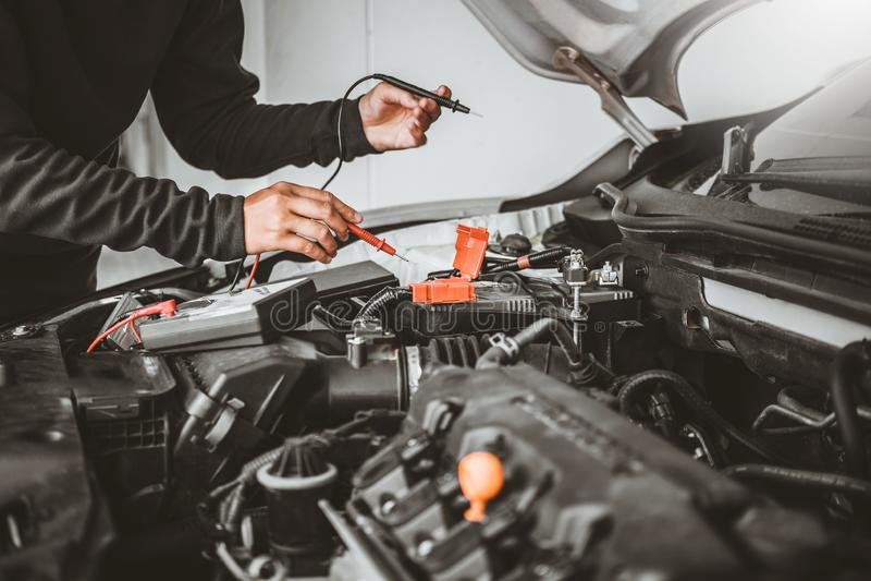 Tecnico Hands del meccanico di automobile che lavora in accumulatore per di automobile di servizio e di manutenzione di riparazio immagine stock libera da diritti