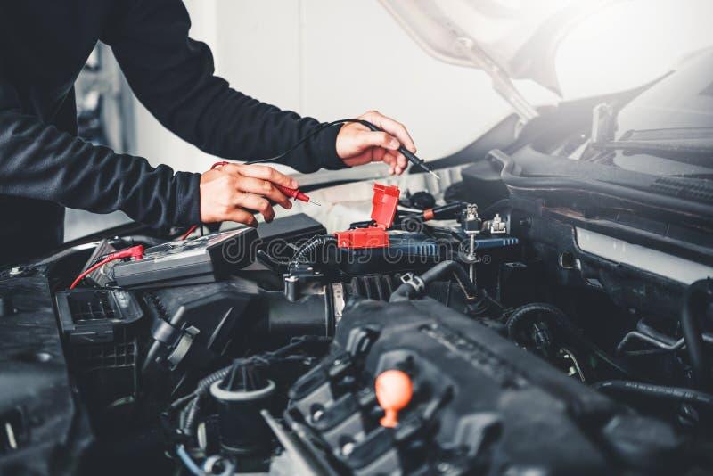 Tecnico Hands del meccanico di automobile che lavora in accumulatore per di automobile di servizio e di manutenzione di riparazio immagini stock libere da diritti