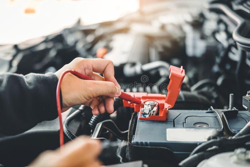 Tecnico Hands del meccanico di automobile che lavora in accumulatore per di automobile di servizio e di manutenzione di riparazio immagine stock