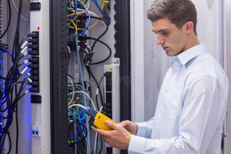 Tecnico messo a fuoco che usando l'analizzatore digitale del cavo sui server fotografia stock