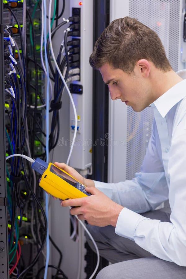 Tecnico serio che usando l'analizzatore digitale del cavo sul server immagini stock libere da diritti