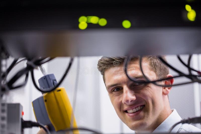 Tecnico sorridente che usando l'analizzatore digitale del cavo sul server immagini stock libere da diritti