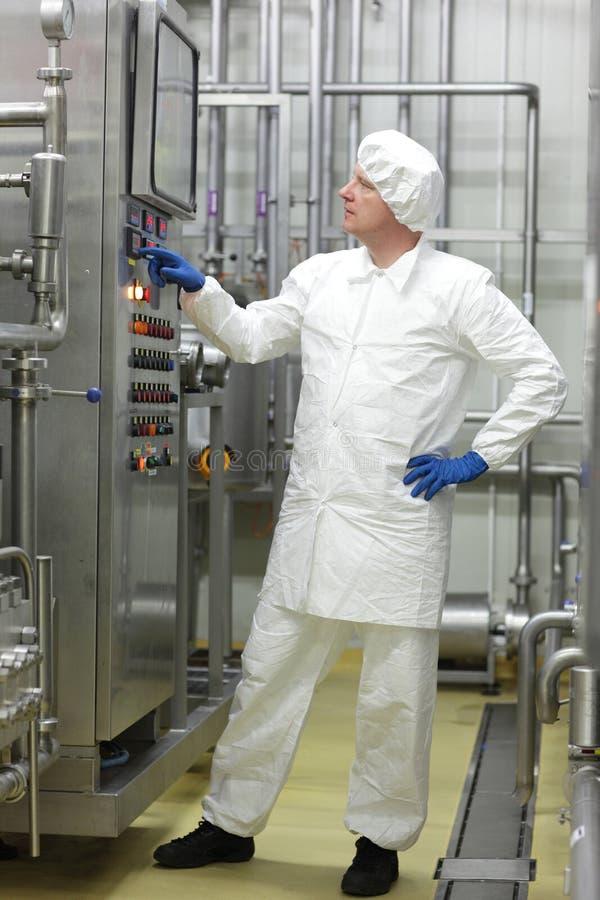 Tecnico in tute bianche e cappuccio che controllano processo industriale in pianta immagine stock