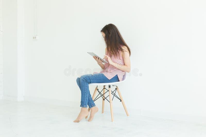 Tecnología, concepto de la gente - mujer joven que se sienta en silla y que lee la tableta digital o que practica surf la red fotos de archivo