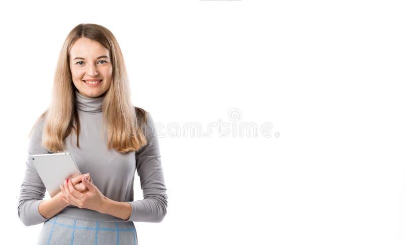 Tecnología de la mujer de negocios del tema Mujer rubia caucásica joven hermosa en el vestido gris que plantea la situación con l fotos de archivo