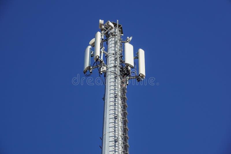 Tecnología en el top de la antena de la torre del G/M 4G de la telecomunicación, transmisor, cielo azul, nubes blancas imagenes de archivo