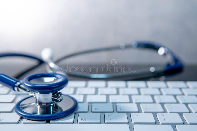 Tecnología médica Estetoscopio en el teclado blanco foto de archivo