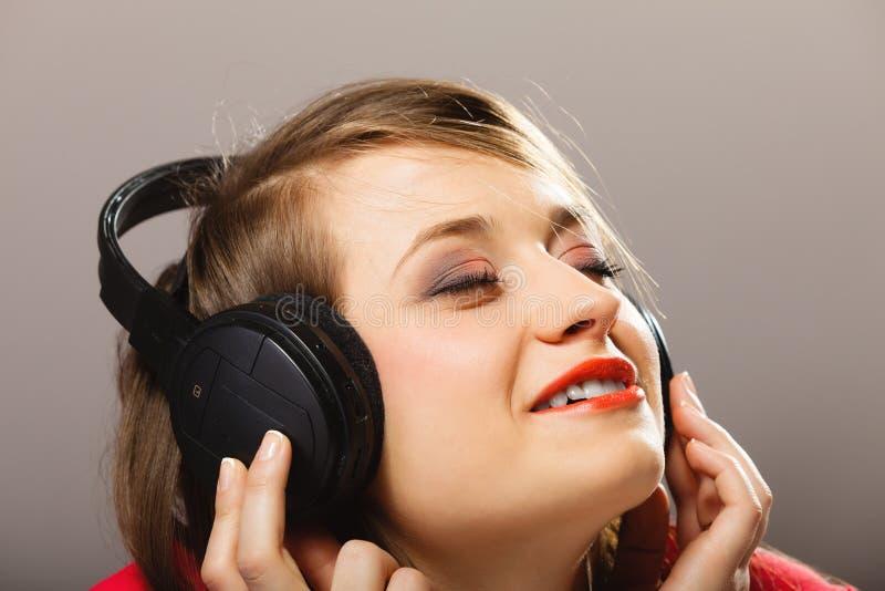 Tecnología, música - chica joven sonriente en auriculares imagen de archivo