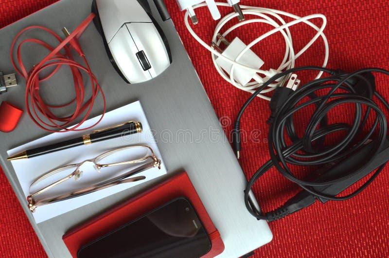 Tecnología para el viaje Ordenador portátil cerrado con los cargadores, el ratón, los vidrios, la pluma, el cuaderno, el teléfono foto de archivo libre de regalías