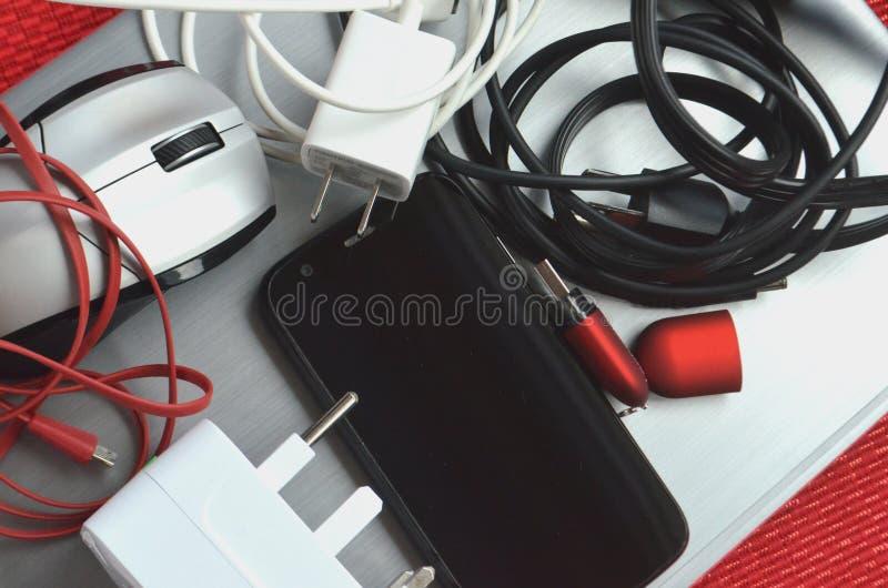 Tecnología para el viaje El ordenador portátil cerrado con los cargadores, el ratón, los vidrios, la pluma, el cuaderno, el teléf fotos de archivo