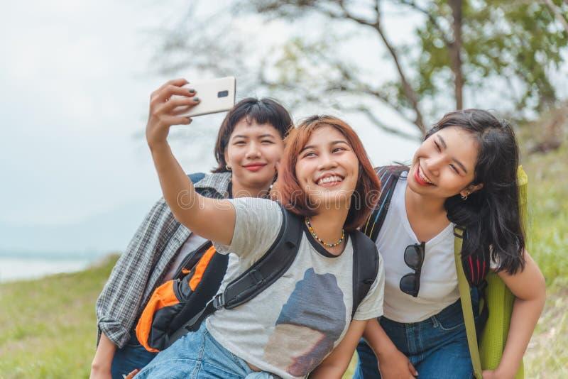 Tecnología, viaje, turismo, alza y concepto de la gente - grupo de la selva de amigos sonrientes con las mochilas que toman el se fotografía de archivo libre de regalías