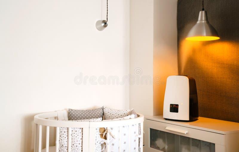 Tecnología y salud Ventile el humectador en el dormitorio de los niños al lado del pesebre recién nacido imagen de archivo