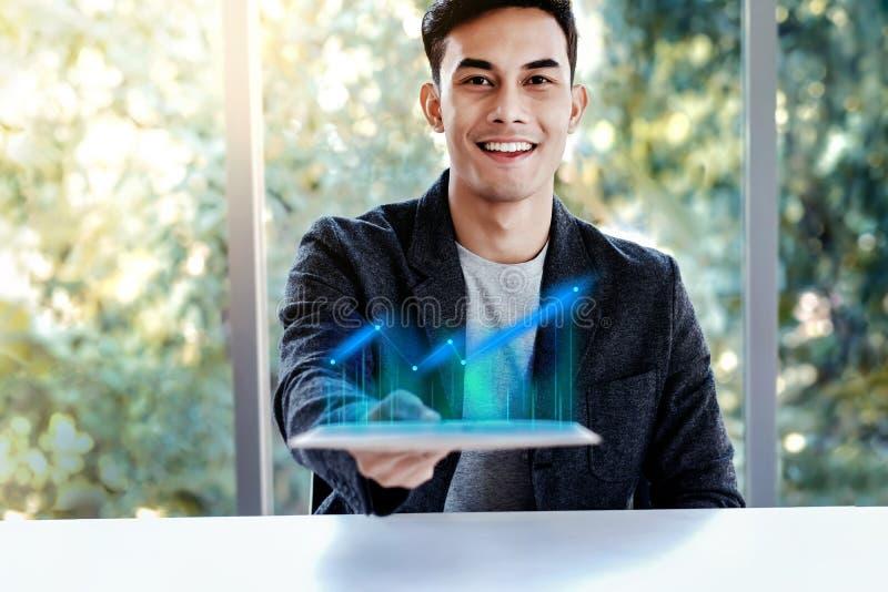 Tecnolog?a en concepto del negocio Hombre joven feliz que se sienta en el escritorio y que presenta el alto gráfico de beneficio  imágenes de archivo libres de regalías