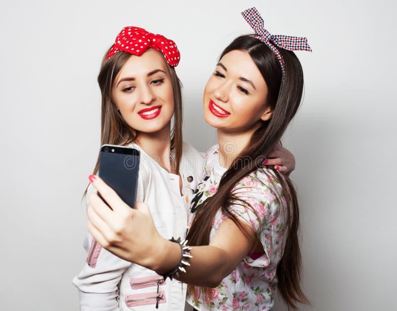 Tecnologia, amizade e conceito dos povos - dois adolescentes de sorriso que tomam a imagem com c?mera do smartphone fotos de stock