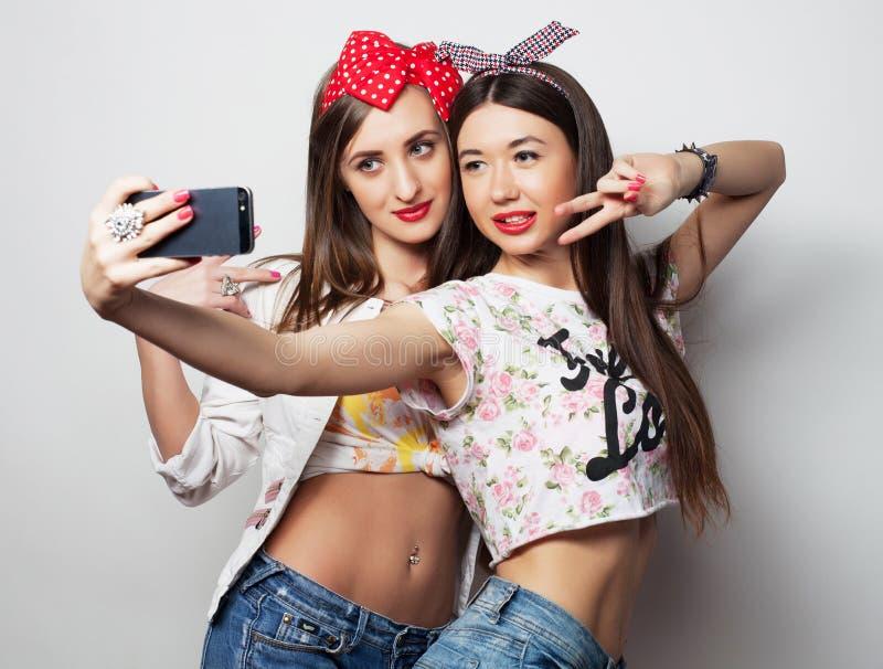 Tecnologia, amizade e conceito dos povos - dois adolescentes de sorriso que tomam a imagem com smartphone fotografia de stock royalty free
