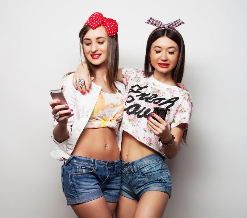 Tecnologia, amizade e conceito dos povos - dois adolescentes de sorriso que tomam a imagem com smartphone imagens de stock royalty free