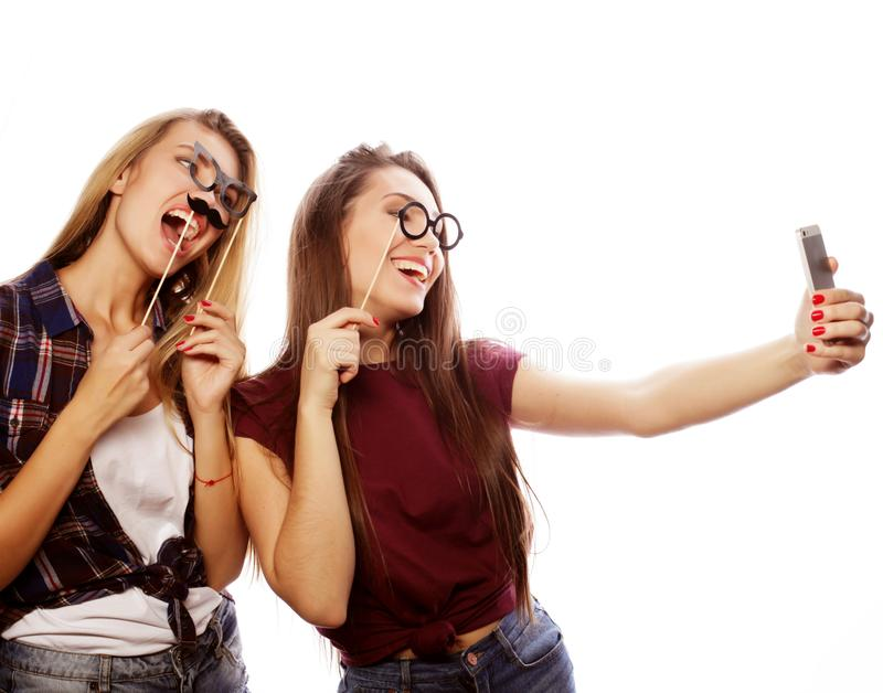 Tecnologia, amizade e conceito dos povos - dois adolescentes de sorriso que tomam a imagem com smartphone foto de stock