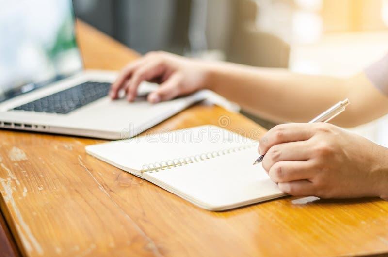 Tecnologia di lavoro del computer portatile dell'uomo e scrivere il posto di lavoro del taccuino fotografia stock libera da diritti