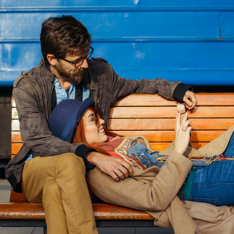 Tecnologia e viagem de Digitas Os pares loving novos no moderno vestem usando o tablet pc ao sentar-se no wai do estação de camin imagens de stock