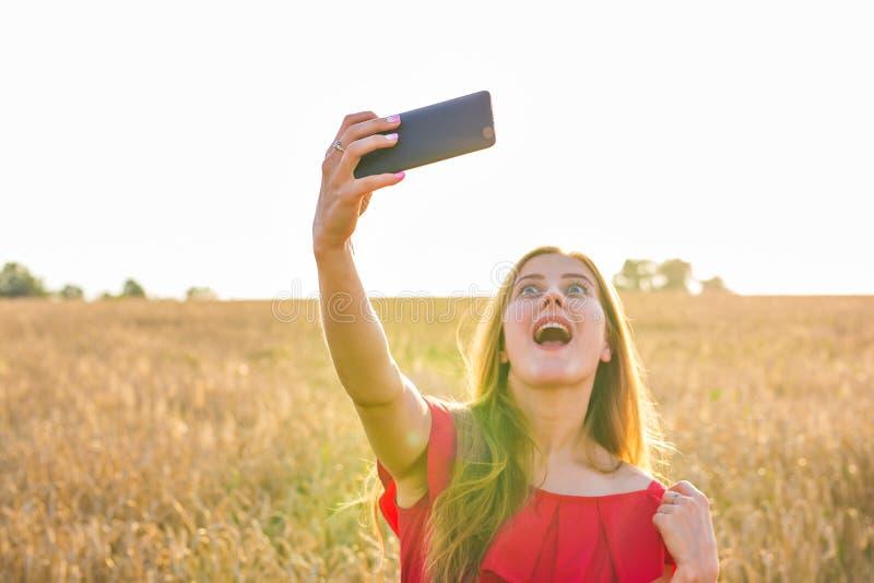 Tecnologia, férias de verão, férias e conceito dos povos - jovem mulher engraçada que toma o selfie pelo smartphone no campo de c foto de stock royalty free
