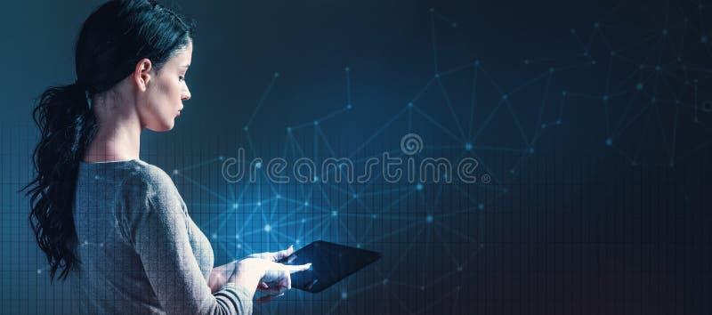 A tecnologia liga com a grade com a mulher que usa uma tabuleta imagem de stock