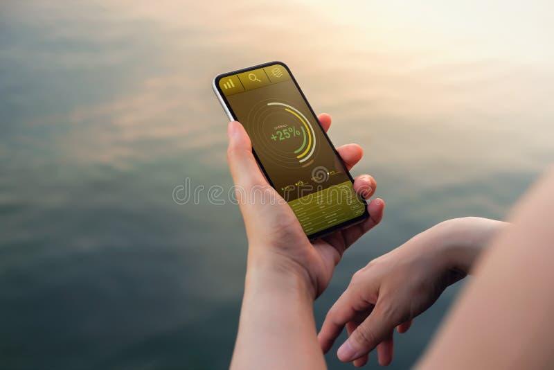 Tecnologia nel concetto di vendita di affari e di finanza I grafici ed i grafici mostrano sullo schermo di Smartphone immagine stock libera da diritti