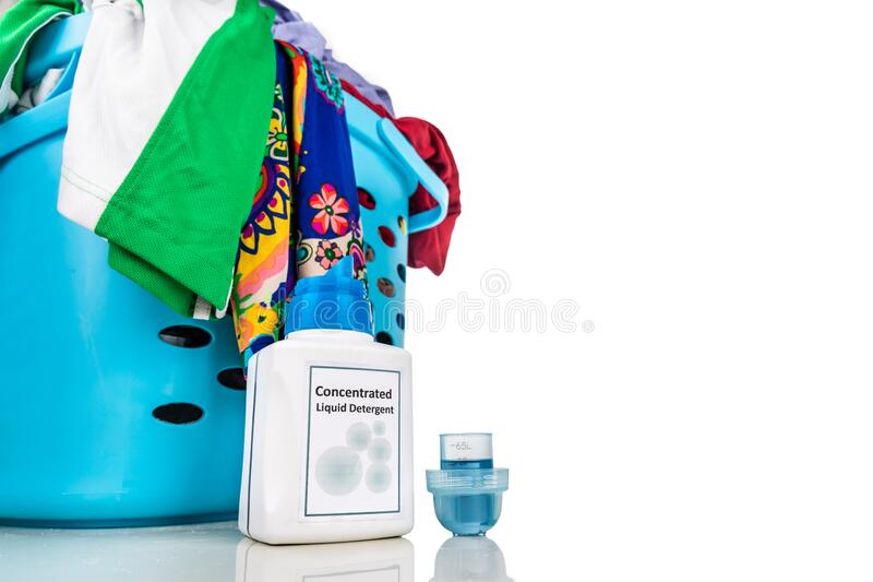 Tecnologically advanced compact concentrated laundry liquid detergent next to basket of clothes royalty free stock images