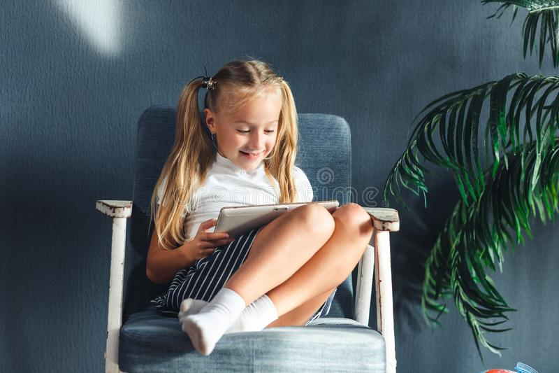 Tecnologie, concetto della gente - giovane ragazza blondy che si siede su una sedia e che guarda la compressa o che pratica il su fotografia stock