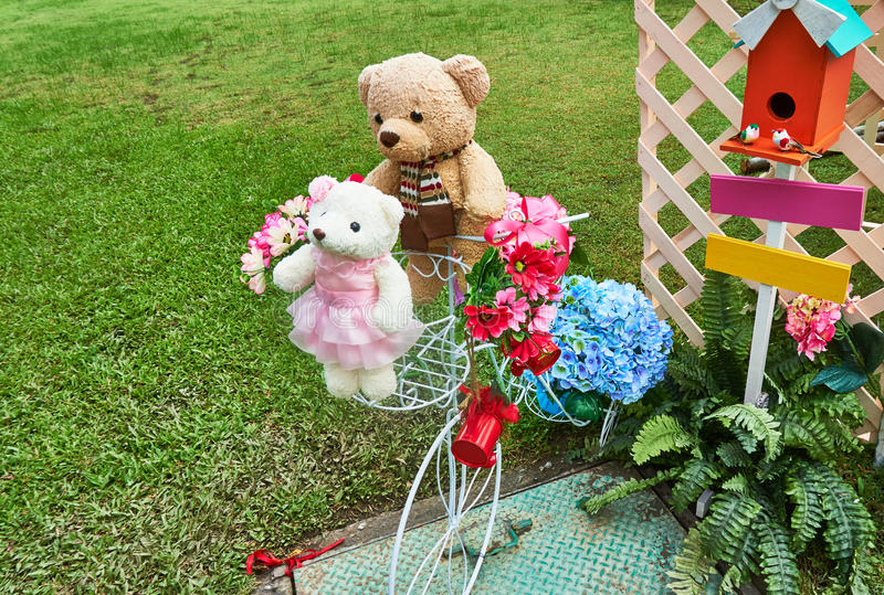 Teddy bares are put near colorful faked flowers. Decorating in garden royalty free stock photo