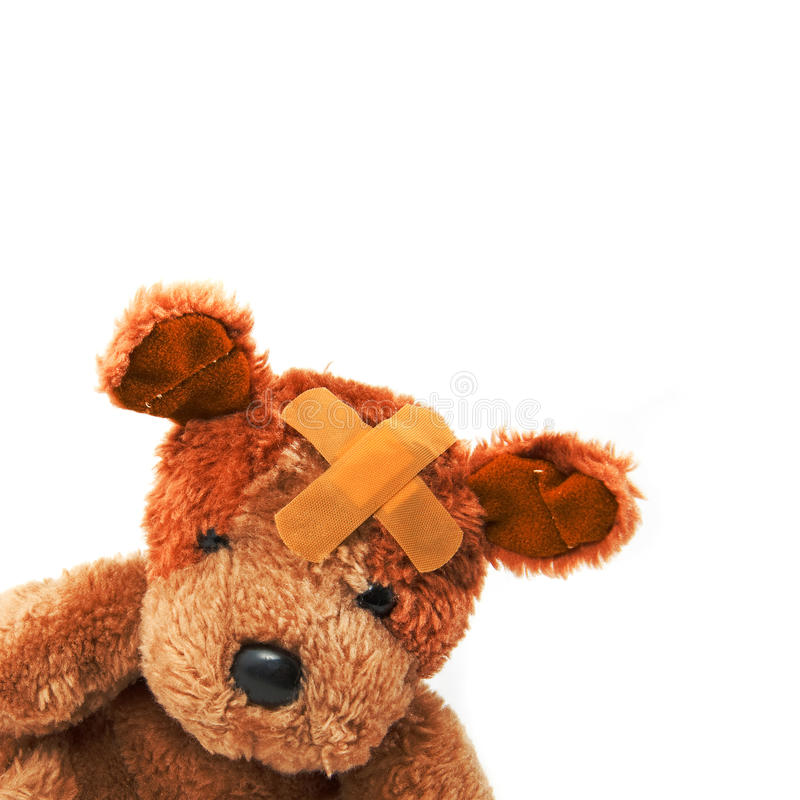 Teddy bear. Cute little teddy bear with plaster on his head over a white background stock image