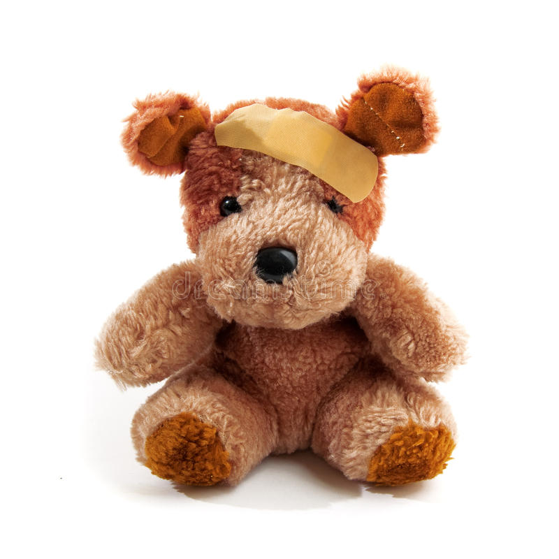 Teddy bear. Cute little teddy bear with plaster on his head over a white background stock images