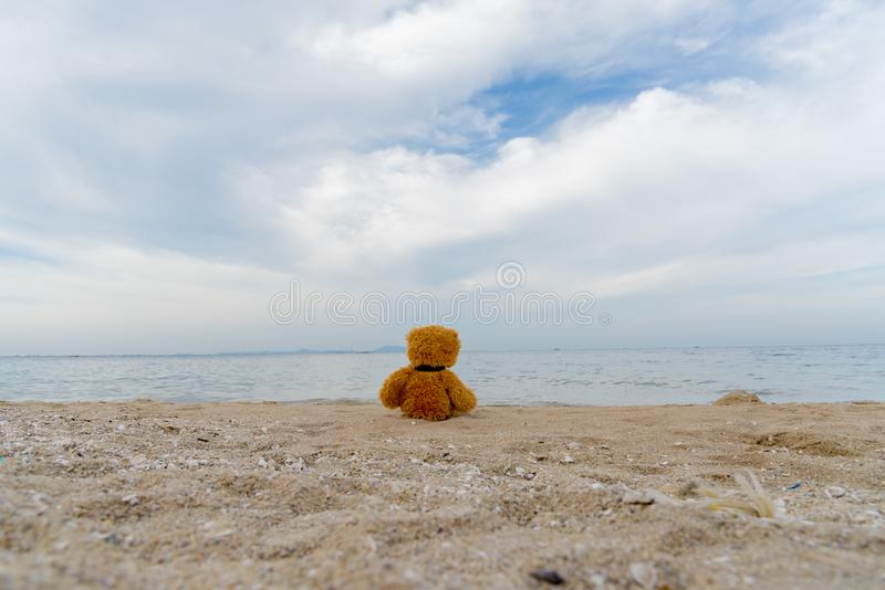 Teddy Bear alone on the beach with the blue sky. Travel concept royalty free stock images
